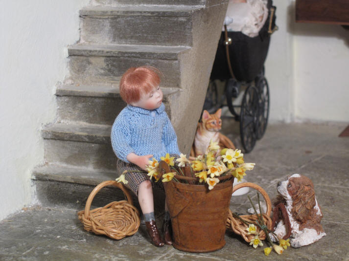 "Robert Alexander is ""helping"" the vicar by putting the daffodils into the two basket in readiness for today's procession."