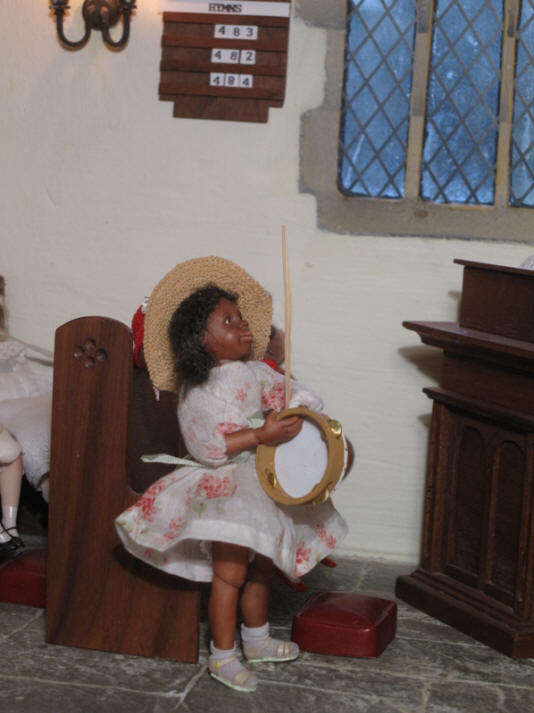 Grace has walked over to the church in order to practice processing with both a palm leaf AND whilst playing her tambourine and singing....