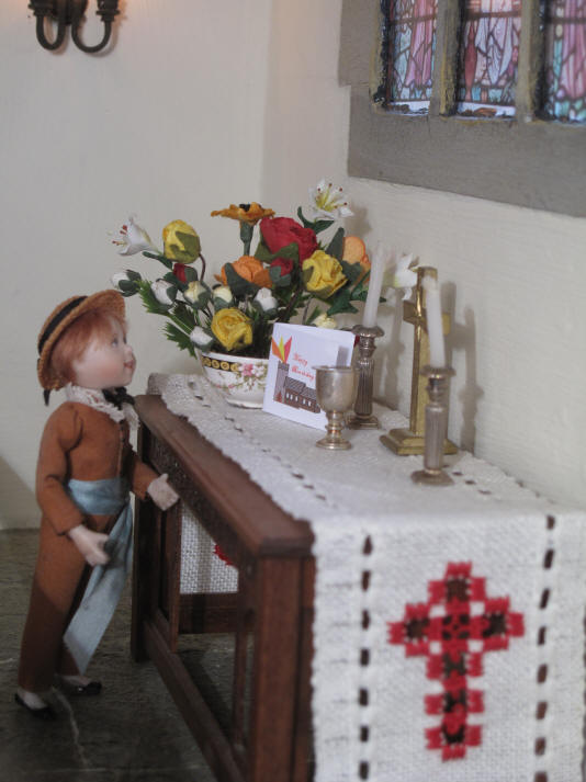 Ben places his card on the altar.  As you can see he has created a picture with his verison of St. Hilary's on it and has put some flames coming out of the tower to represent the Holy Spirit as a fire.